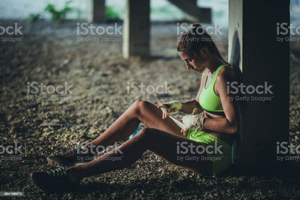 Tired sportswoman unwrapping bandage after finishing sports training in a ruin. royalty-free stock photo