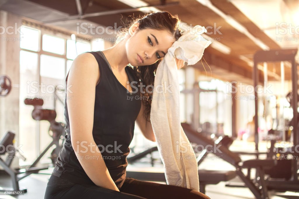 Tired sporty girl wiping sweat with towel at gym. stock photo