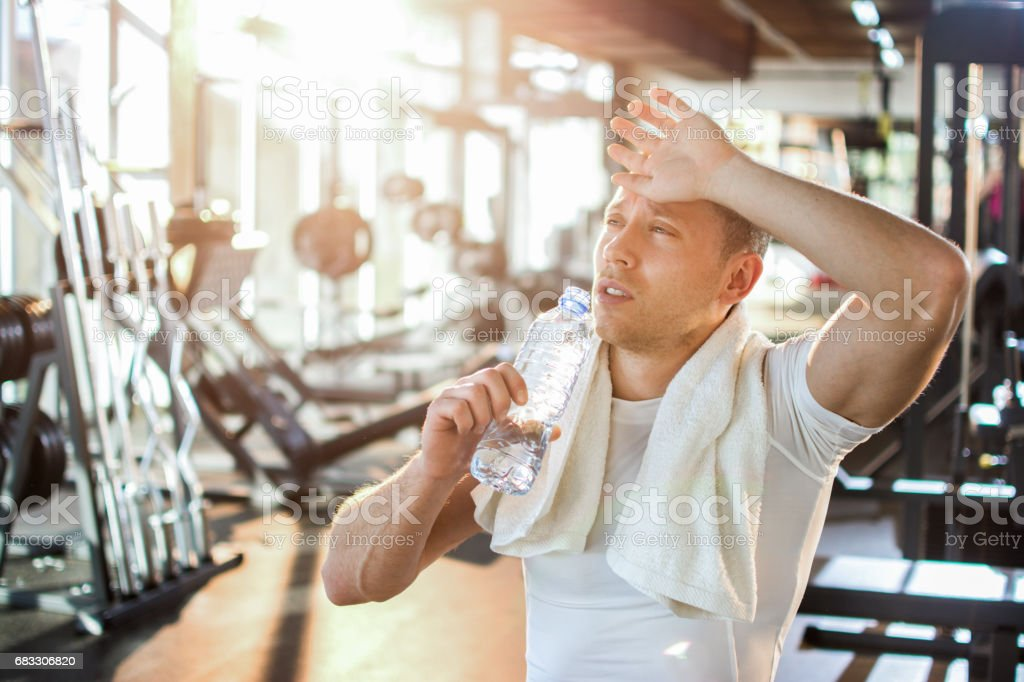 Tired sporty man drinking water at gym. foto stock royalty-free