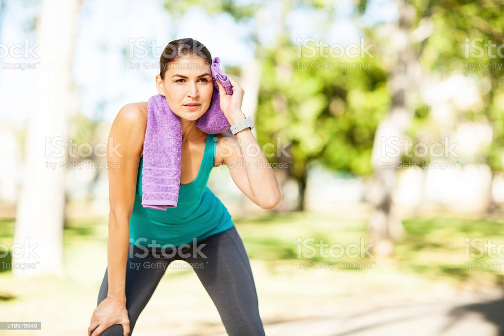 Tired Sporty Woman Wiping Sweat With Towel In Park stock photo