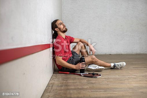 Young exhausted man taking a break from racketball.
