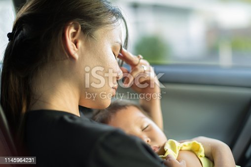 A unhappy exhausted mom trying to take a nap with her baby in the car.