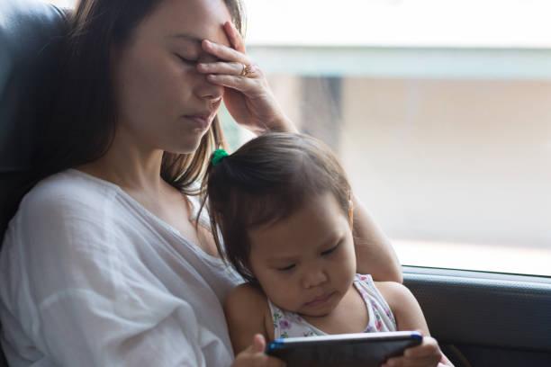 vermoeide beklemtoonde moeder die een dutje met haar kind neemt. - alleenstaande moeder stockfoto's en -beelden
