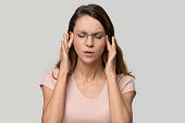 istock Tired stressed young woman feeling strong headache massaging temples 1126440402