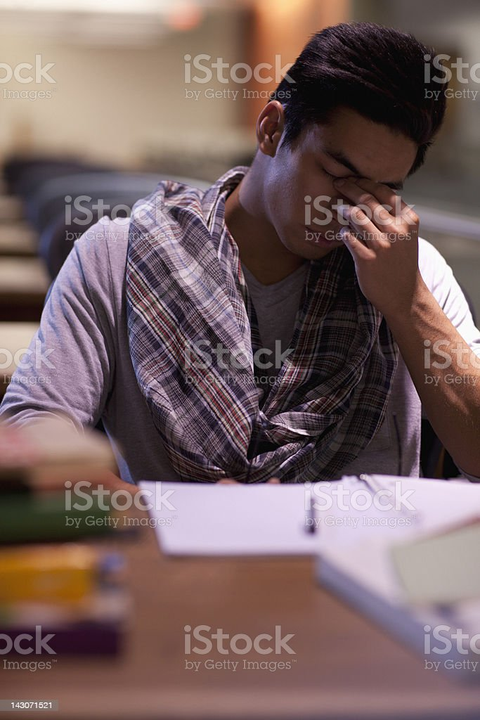 Tired student at work in library royalty-free stock photo