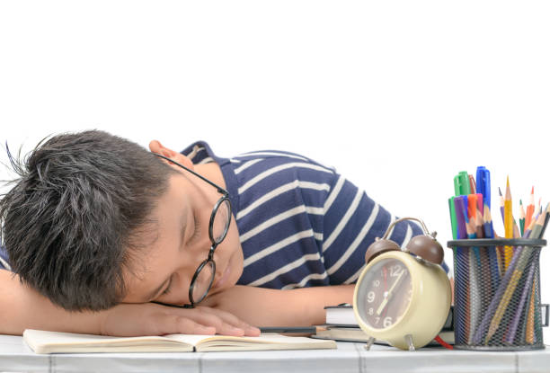 Tired student boy with glasses sleeping on the books stock photo