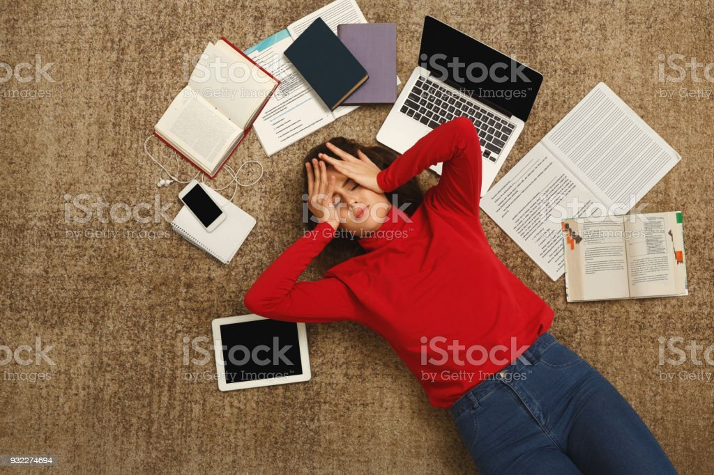 Tired student girl lying on the floor with books and gadgets stock photo