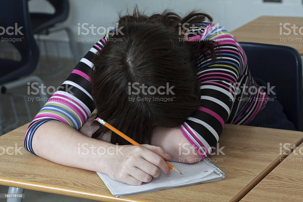 Tired student lays her head down in classroom royalty-free stock photo