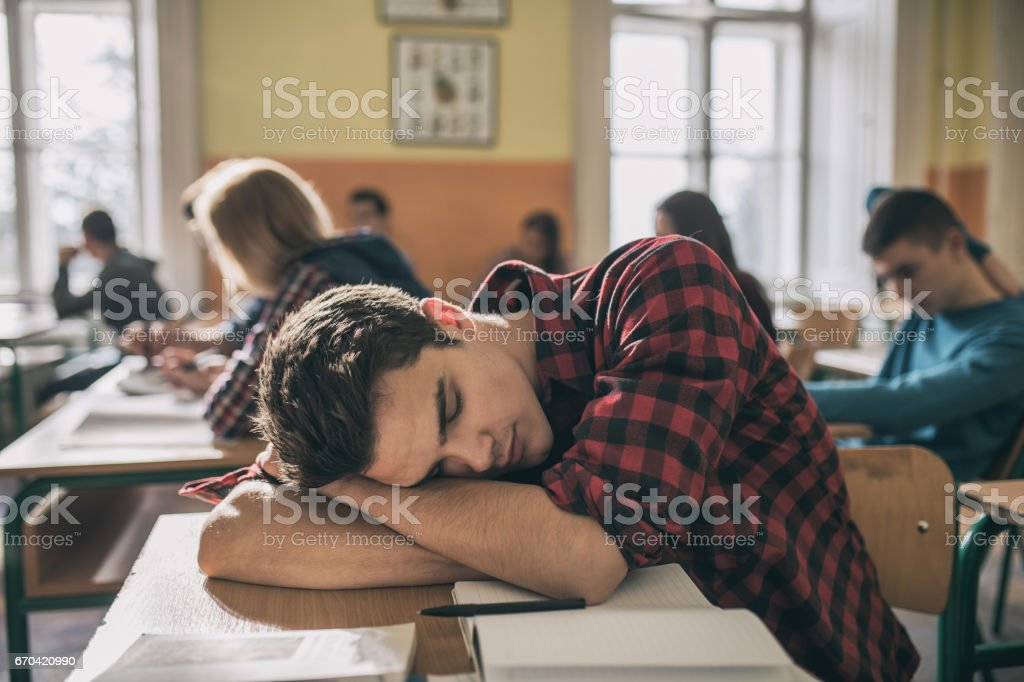 Tired student taking a nap during a lecture in the classroom. stock photo