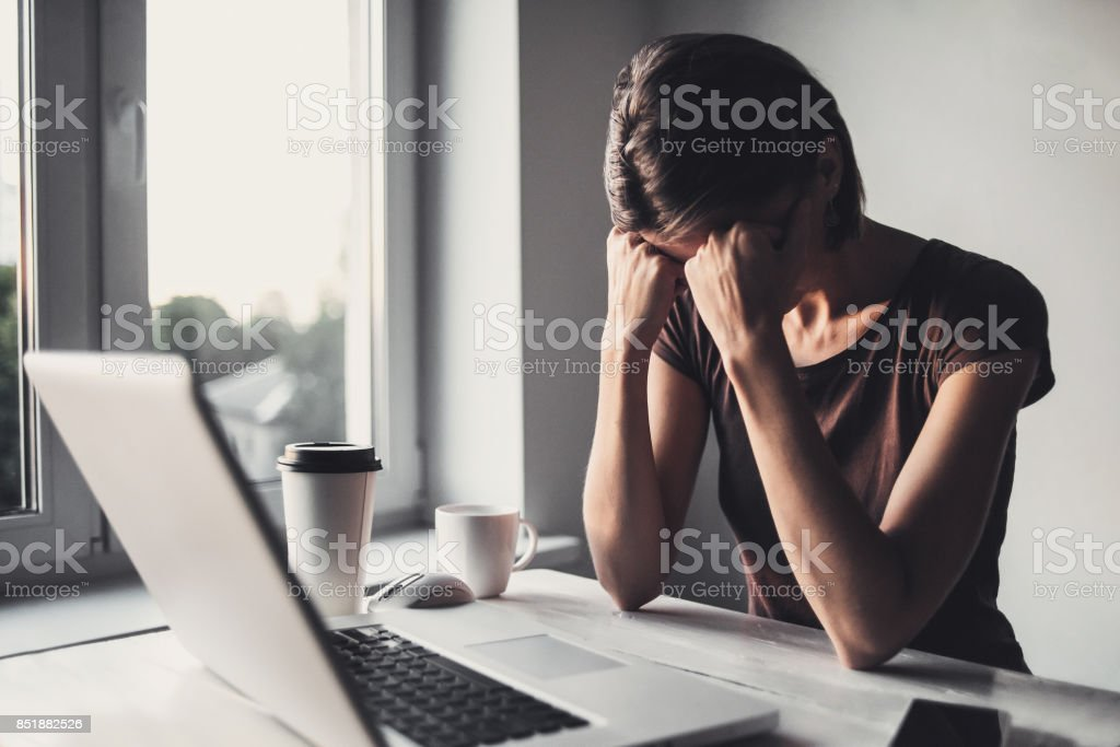 Tired student with laptop and coffee stock photo