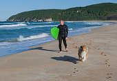 Tired surfer with collie dog friend carry surfboard