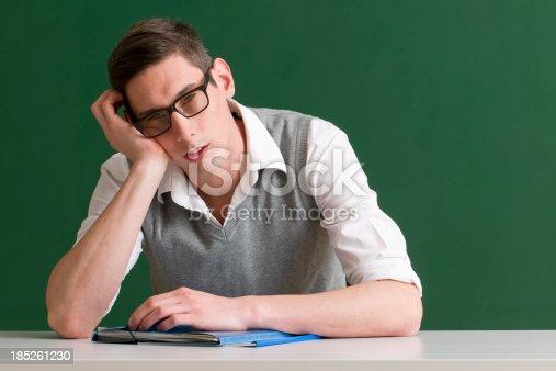 840623374 istock photo tired teacher at blackboard 185261230