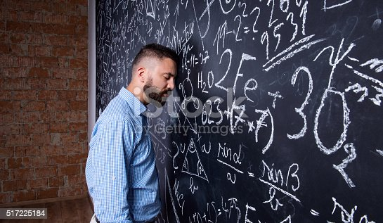 istock Tired teacher sleeping against big blackboard with mathematical 517225184