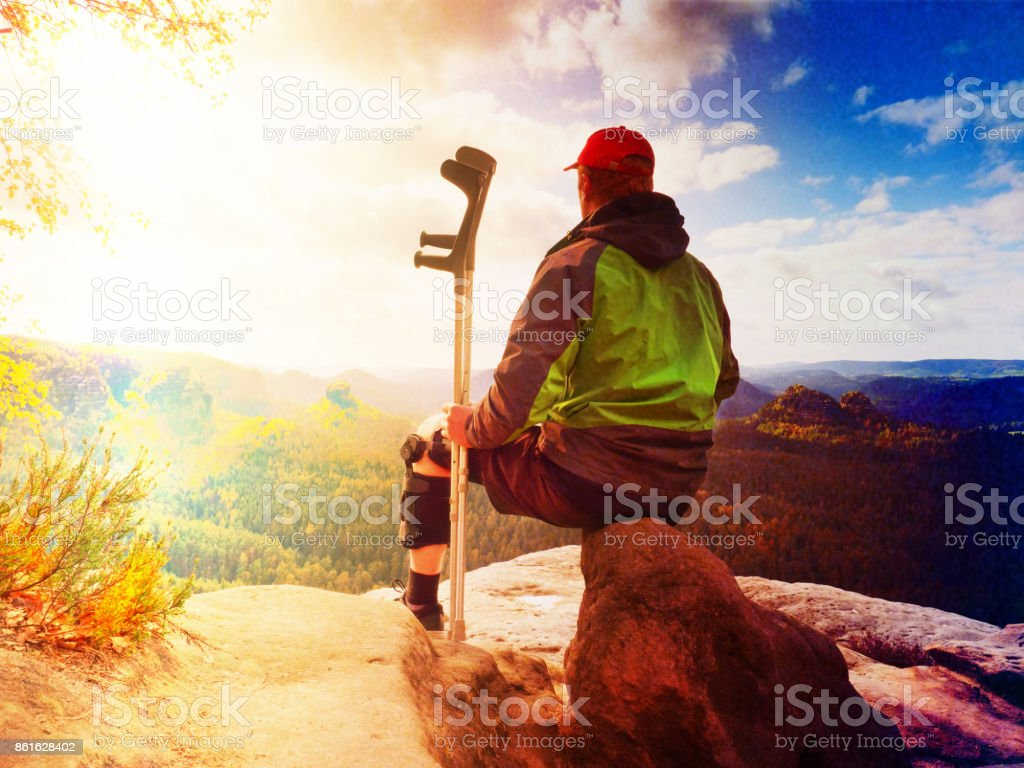 Tired tourist with medicine crutch  and broken leg fixed in immobilizer resting on  mountain summit. Valley bellow sitting man in green windcheater stock photo