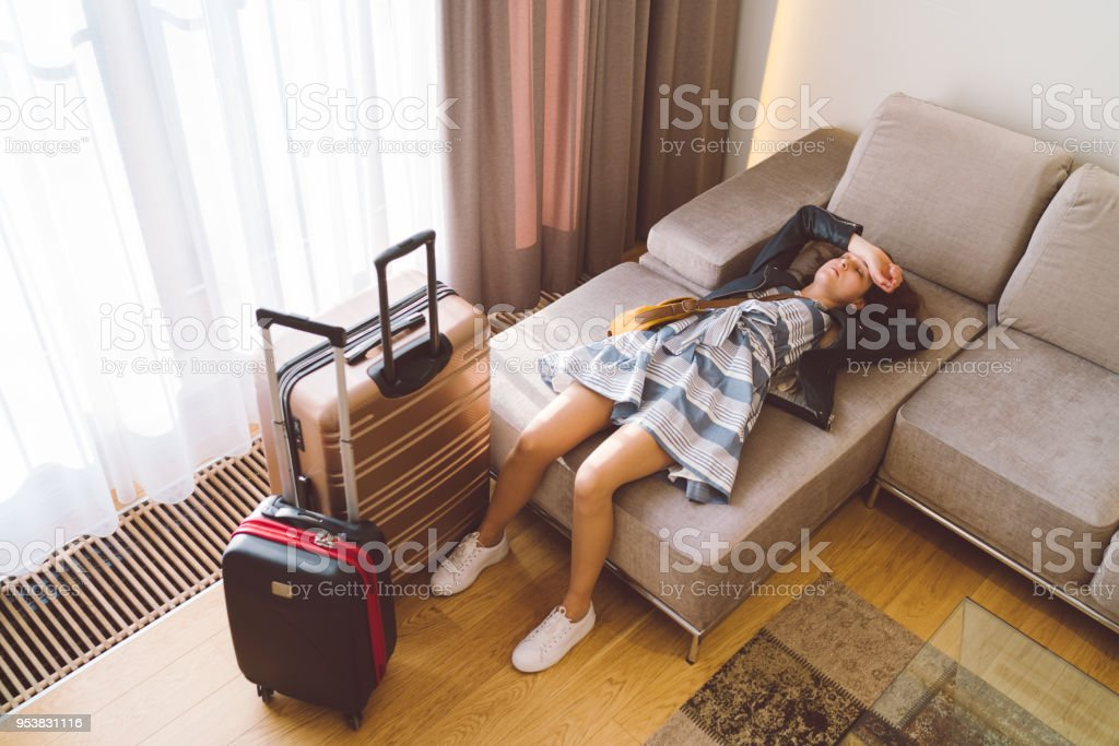 Tired tourist woman resting in the hotel room stock photo