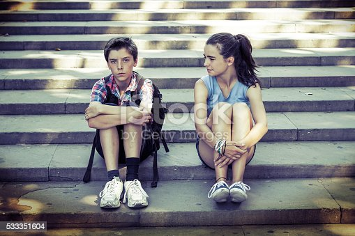 istock tired travelling siblings sitting on steps 533351604