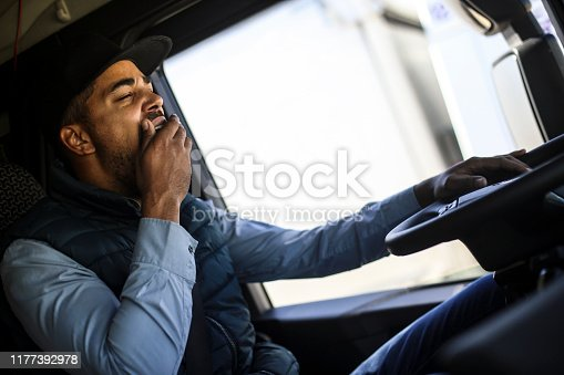 Truck driver yawning. About 35 years old, African male.