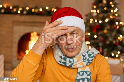 Tired unhappy annoyed old man being sick on Christmas eve, suffering from headache, keeping hand on forehead, wearing yellow shirt and santa hat, looks at camera with upset expression.