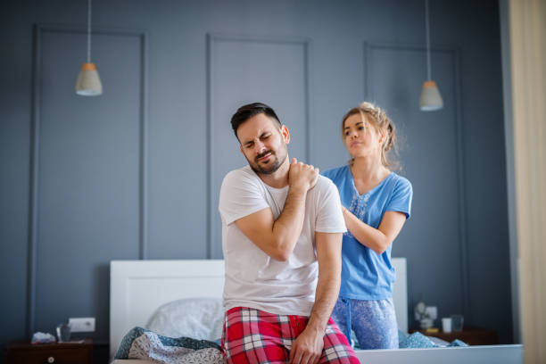 Tired unhappy man holding his neck after bad sleep while his wife looking sadly to him and helping with massage. stock photo