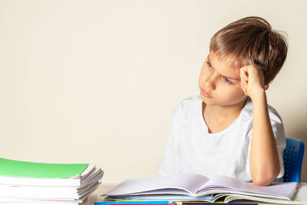 Tired upset schoolboy with pile of school books and notebooks Upset schoolboy with pile of school books and notebooks illiteracy stock pictures, royalty-free photos & images