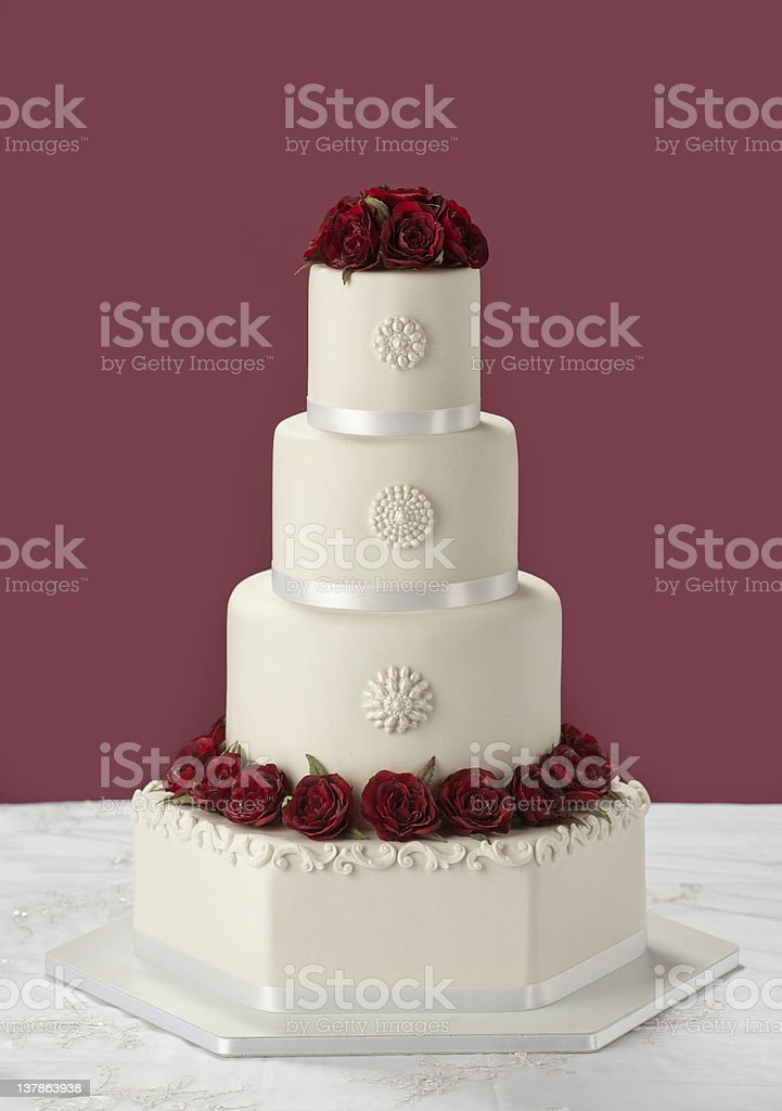 tired wedding cake with red roses stock photo