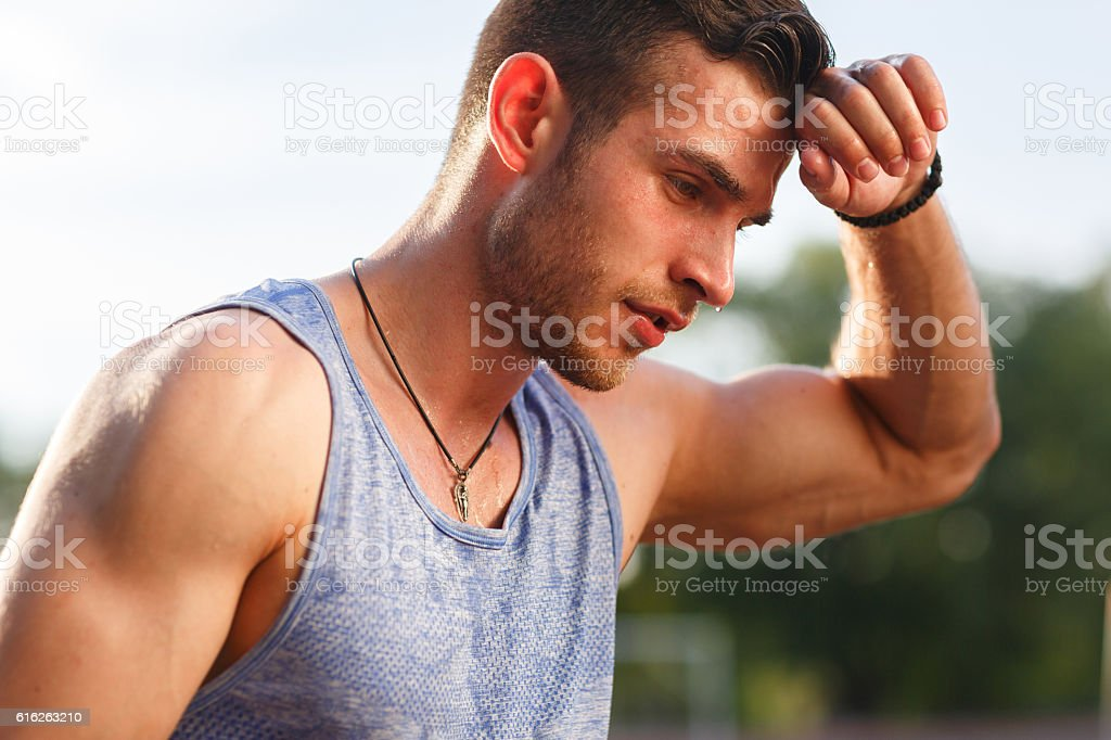 Tired wet athletic man wiping sweat his hand stock photo