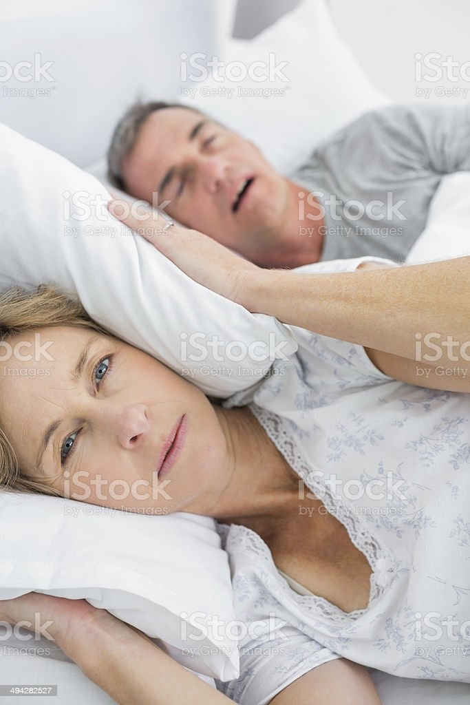 Tired wife blocking her ears from noise of husband snoring stock photo