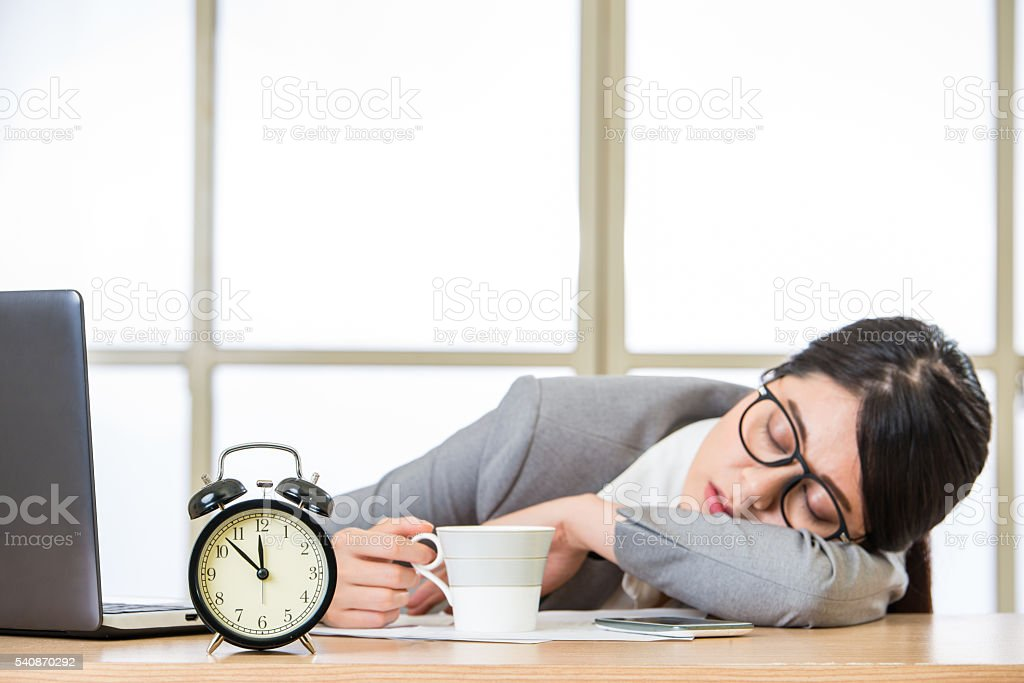 Tired woman are sleeping and holding coffee stock photo