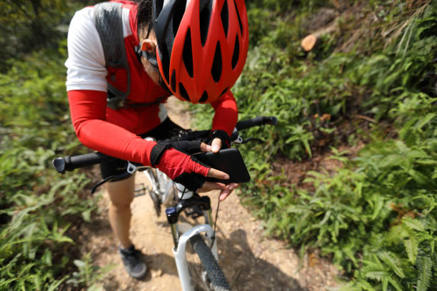 Tired woman cyclist have a rest with mobie phone in hands Tired woman cyclist have a rest with mobie phone in hands female biker resting stock pictures, royalty-free photos & images