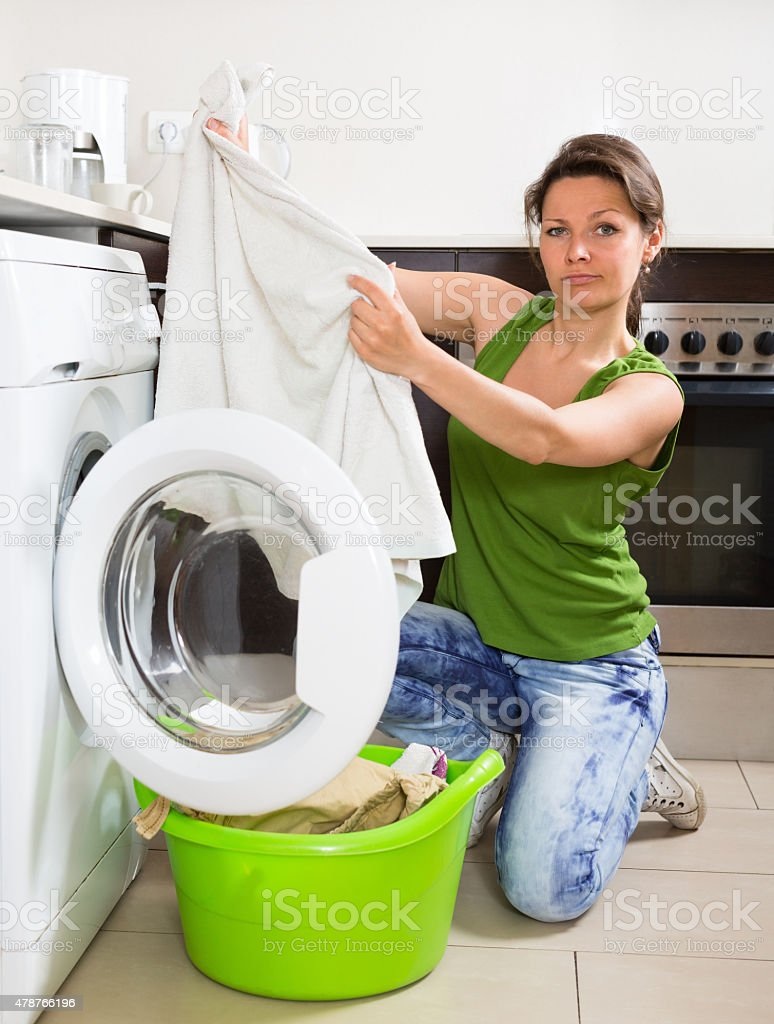Tired woman doing laundry at home stock photo