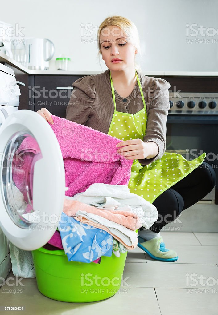 Tired woman doing laundry stock photo