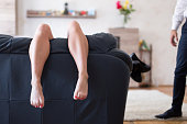 Tired woman hanging legs on sofa in living room