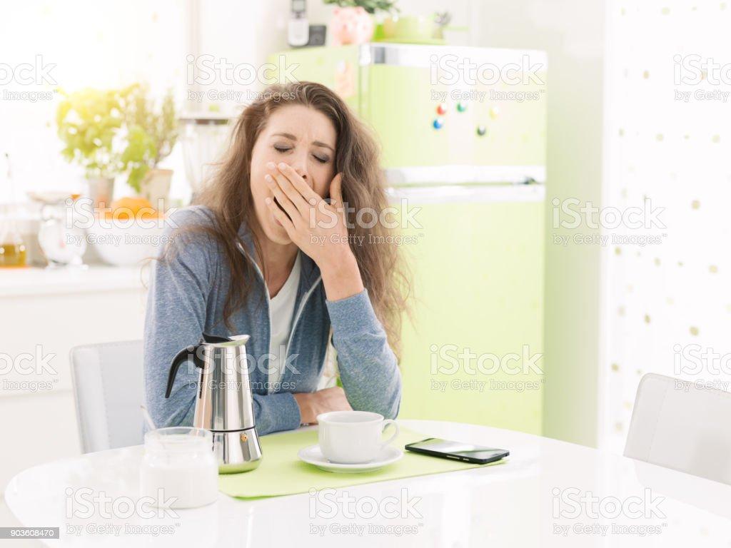 Mujer cansada de desayunar en casa - foto de stock