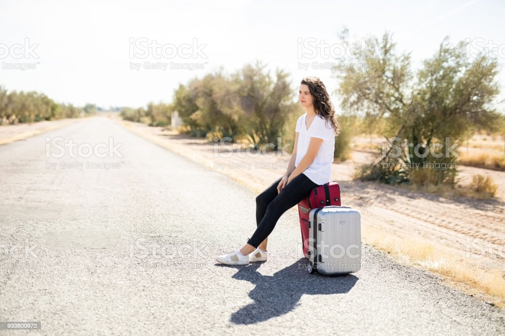 Tired woman hitchhiker with suitcase on road stock photo