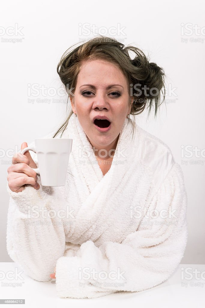 tired woman holding coffee cup in her hand stock photo