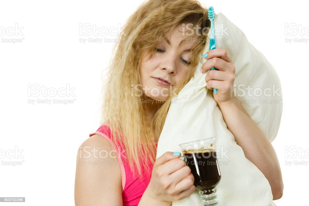 Tired woman holding toothbrush and coffee stock photo