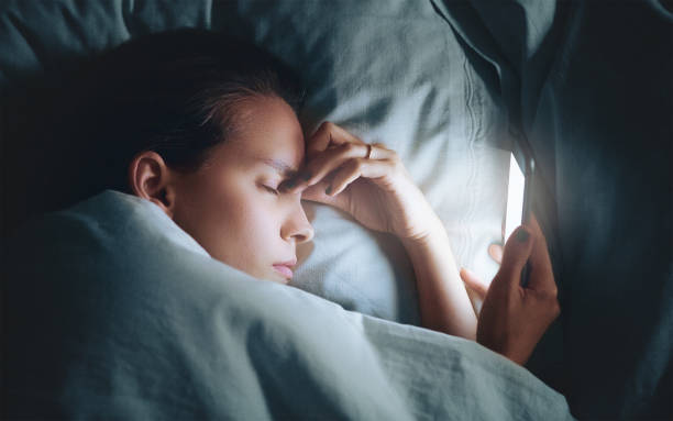 Tired woman in bed with smartphone stock photo