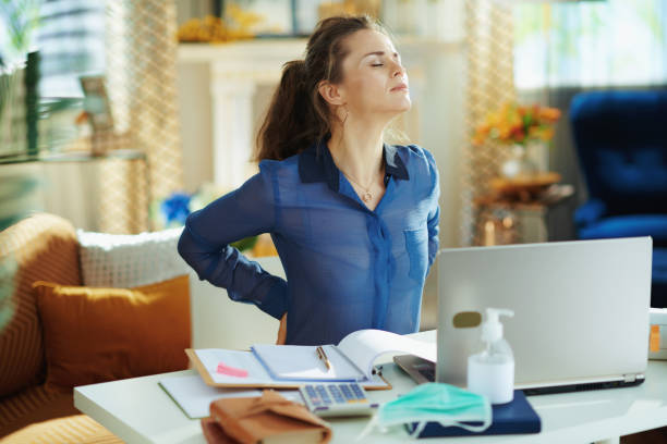 tired woman in modern house in sunny day having back pain tired modern woman in blue blouse in the modern house in sunny day having back pain in temporary home office during the coronavirus epidemic. back pain stock pictures, royalty-free photos & images
