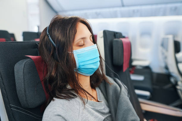 tired woman in virus protection face mask sleeping in empty airplane - covid flight imagens e fotografias de stock