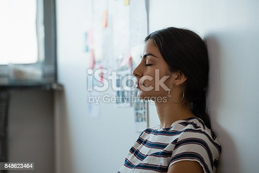Tired young woman leaning on wall in creative office