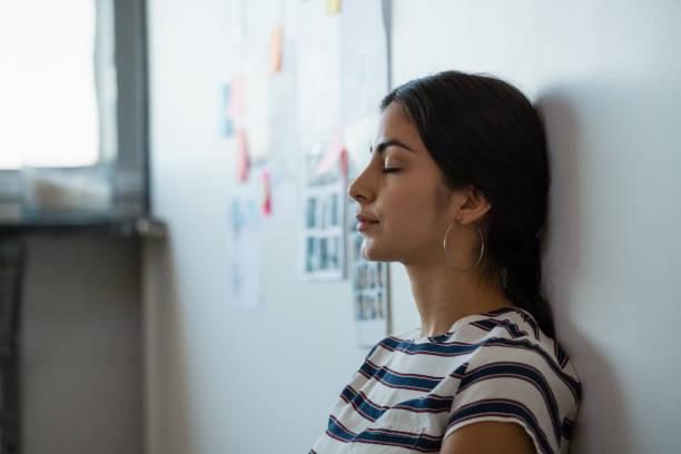 tired woman leaning on wall in office - appoggiarsi foto e immagini stock