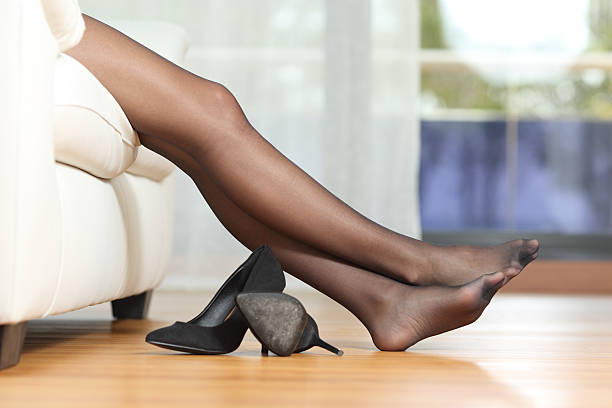tired woman legs resting on couch - black women wearing pantyhose stock photos and pictures