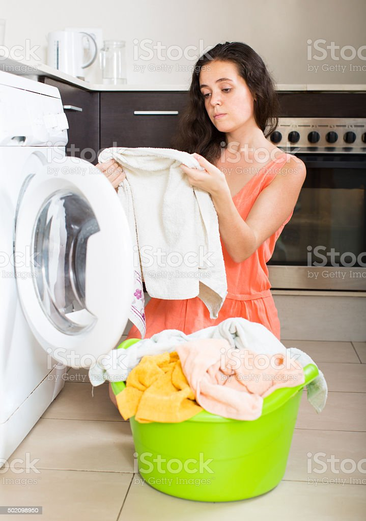 Tired woman near washing machine stock photo