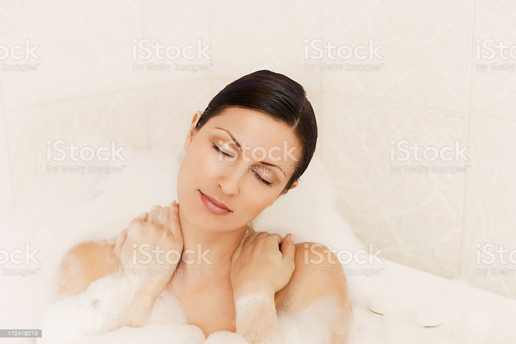 Tired woman relaxing in a bubble bath with eyes closed