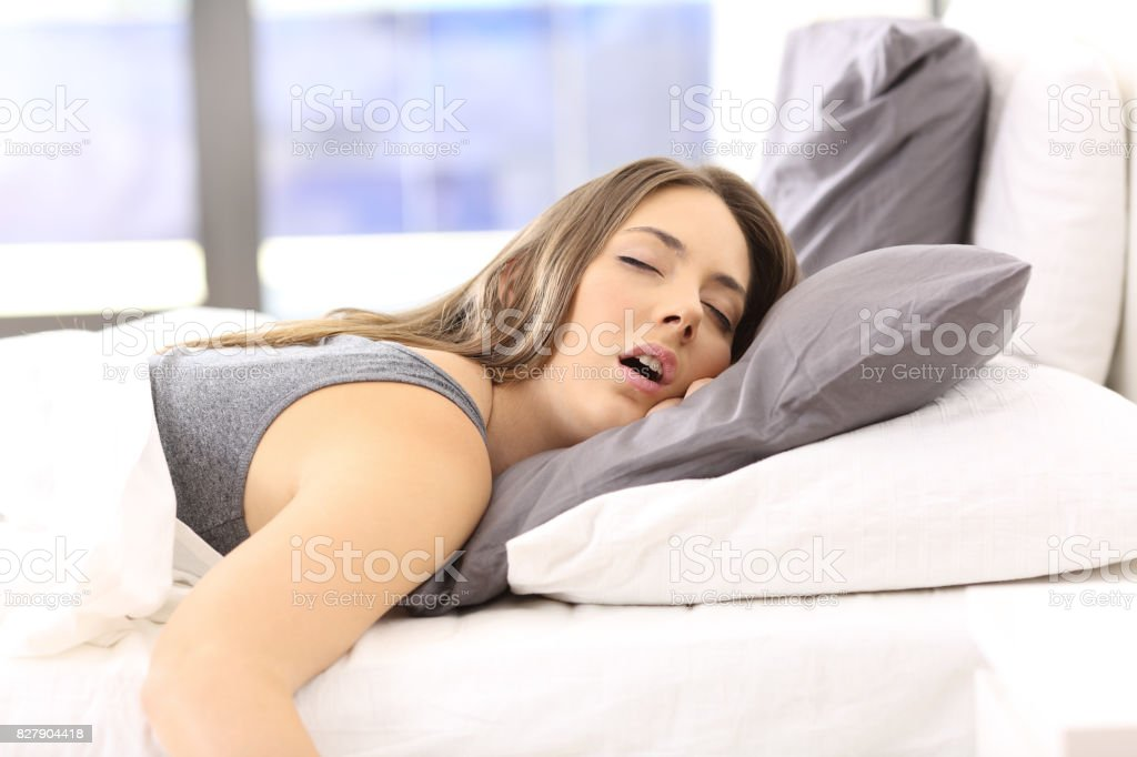 Tired woman resting on a bed at home stock photo