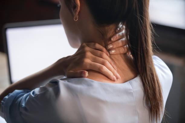 mujer cansada frotando el cuello dolorido rígido, vista trasera de cerca - espalda humana fotografías e imágenes de stock
