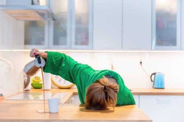 tired woman sleeping on the table in the kitchen at breakfast. trying to drink morning coffee - senny zdjęcia i obrazy z banku zdjęć
