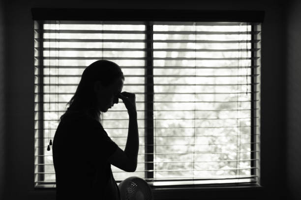 Tired woman standing next to bedroom window. stock photo