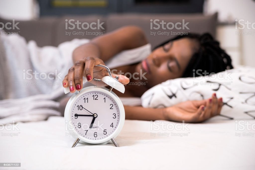 Tired woman switching off her alarm clock in her bedroom stock photo