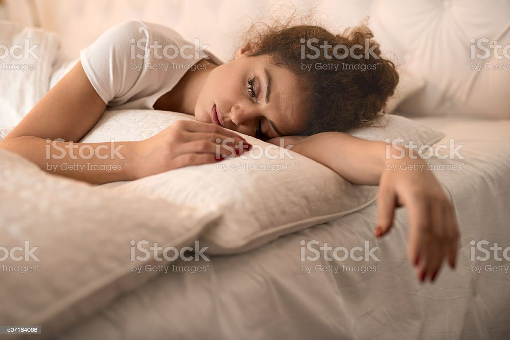 Tired woman taking a nap in a bed. stock photo